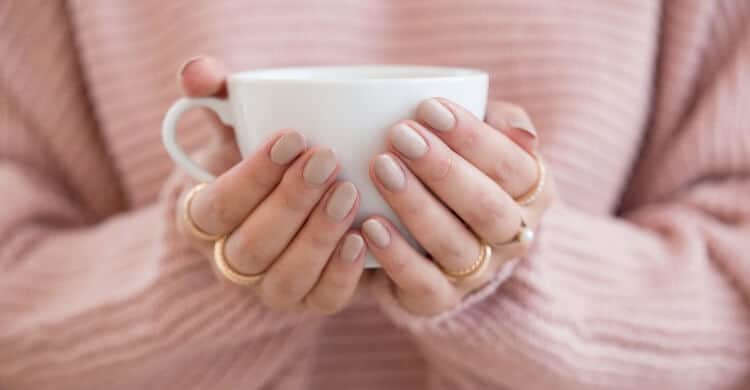 Woman in pink holding coffee cup