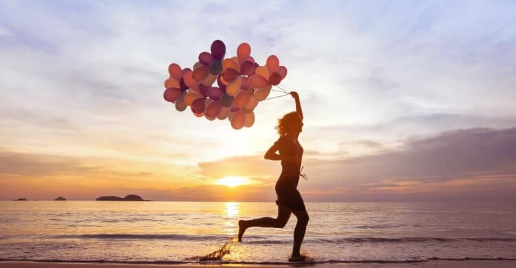 Woman running on beach with balloons
